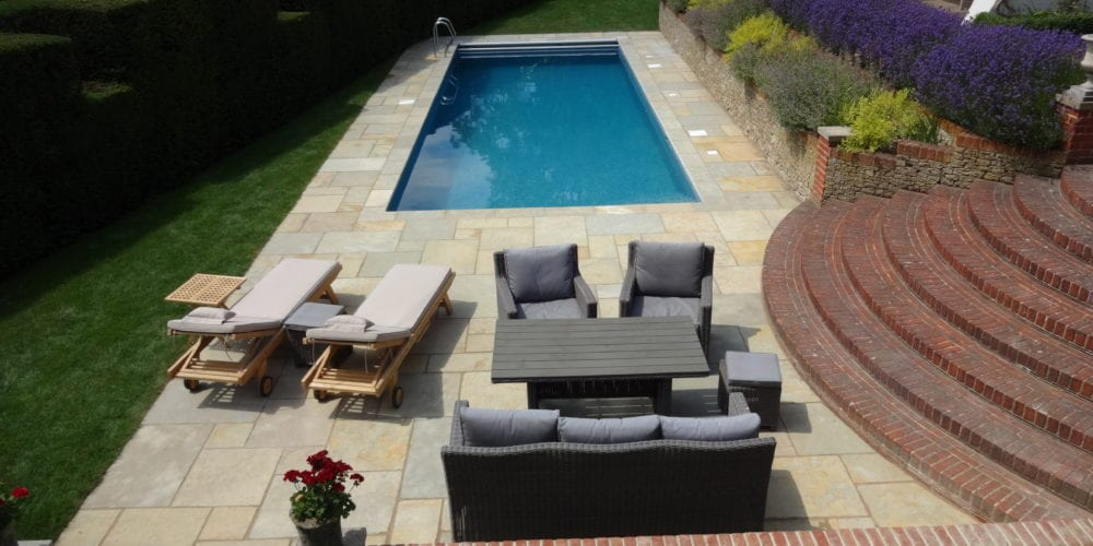 Simple outdoor swimmming pool with paving and furntiure