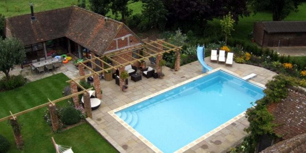 Swimming pool with paving and slide