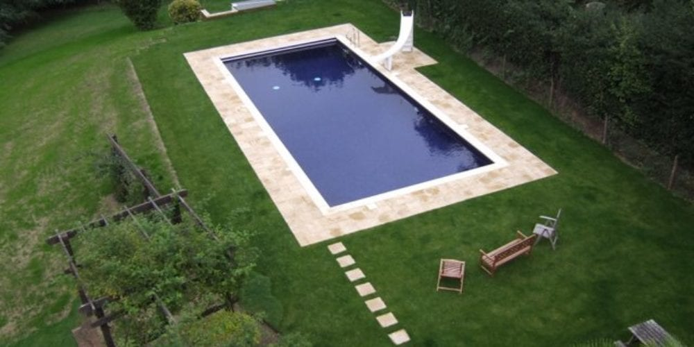 Aerial photo of swimming pool with paving and pathway