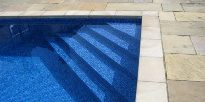 Corner steps of swimming pool with blue mosaic tile