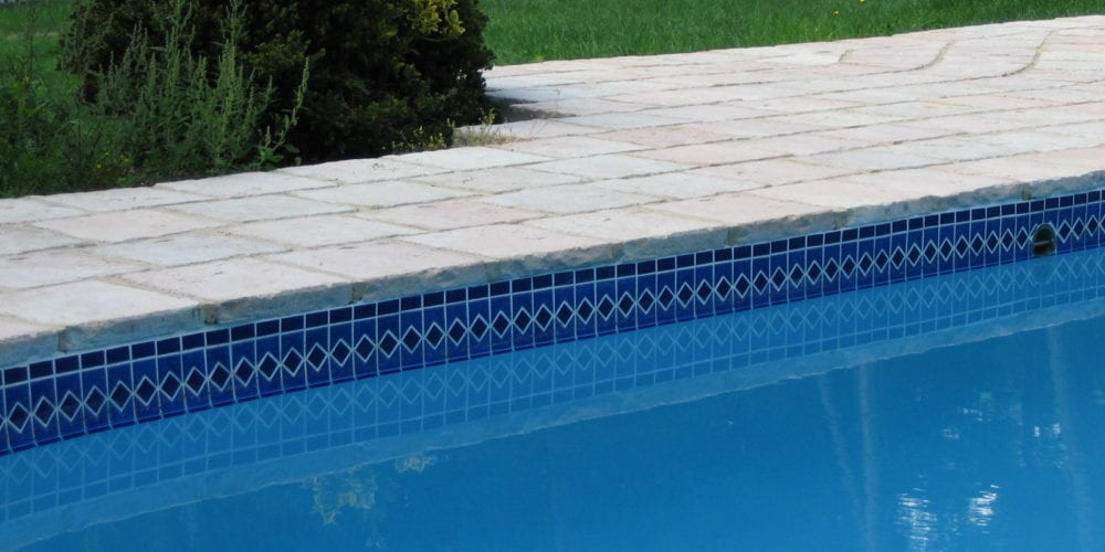 Simple tiled swimming pool with rustic paving