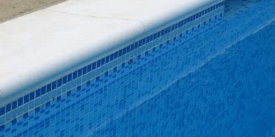 Close up of rounded coping and mosaic tile pool