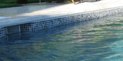 Mosaic tile pool installation with coping