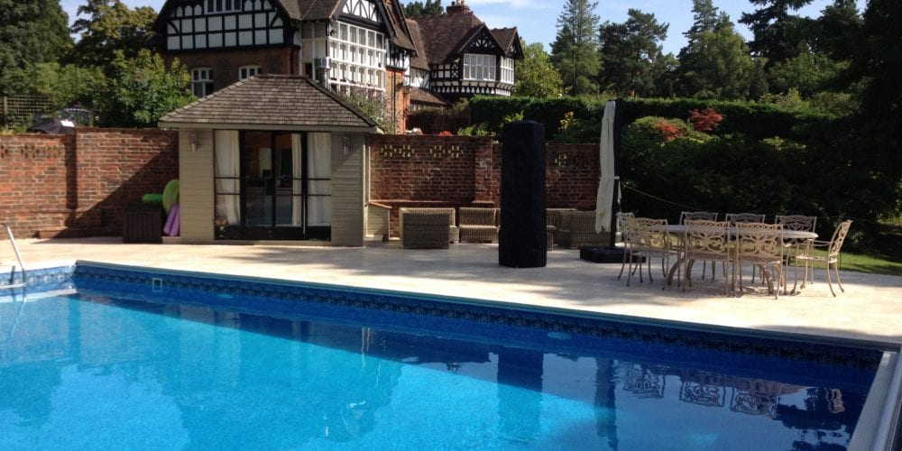 Outdoor swimming pool in Surrey with surround and mosaic tile
