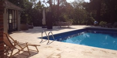Paving pool surround in Surrey with deckchair and grabrail