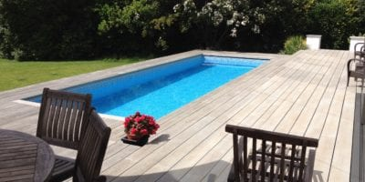 Modern wood panel surround on outdoor swimming pool with mosaic tile