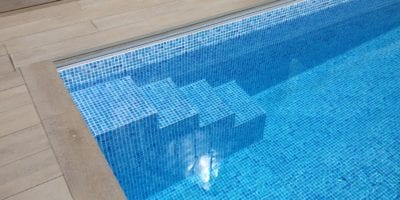 Close up of mosaic tile outdoor swimming pool with steps