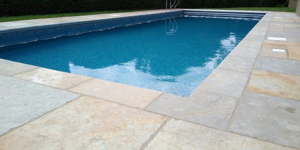 Outdoor swimming pool in Surrey with mosaic tile and grabrail