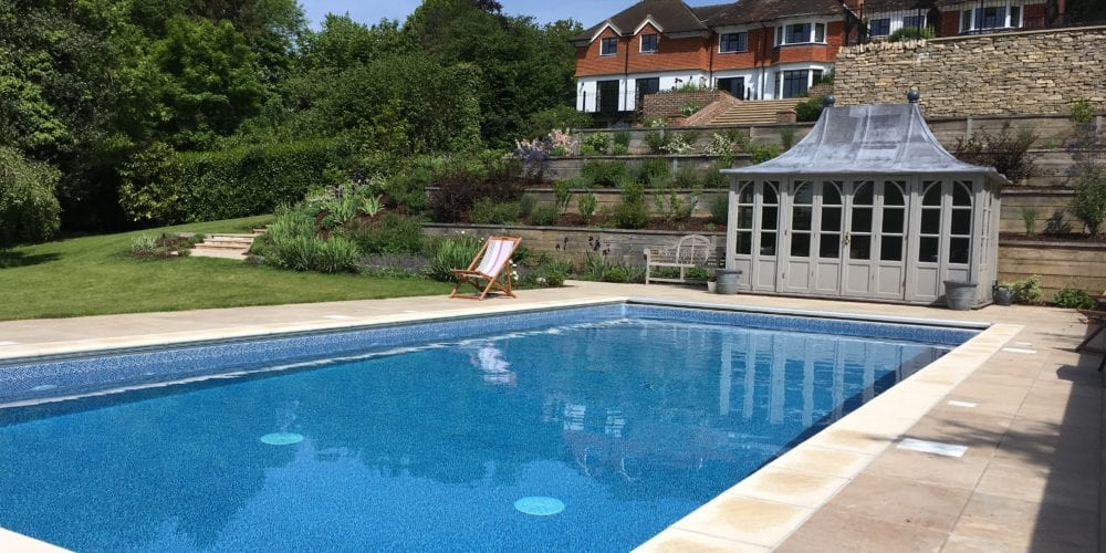 Outdoor pool installation with new coping and pool house