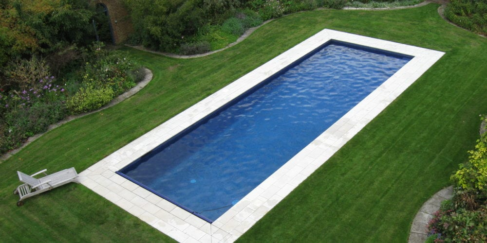 Swimming pool in lawn with white paving
