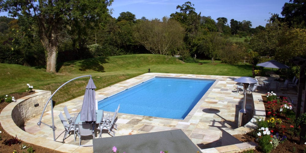 Surrey outdoor swimming pool installation with paving